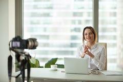 Vlogger focalisé sûr de femme d'affaires parlant au filmin de caméra photos stock