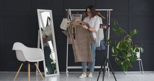 Vlogger presenting new dress and accessory while recording video on mobile phone. Female boutique owner presenting new dress and accessory while recording video stock video