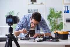 The vlogger recording computer repair on camera for vlog blog. Vlogger recording computer repair on camera for vlog blog Royalty Free Stock Photos