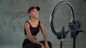 Vlogger sonriente joven de la mujer que habla, mostrando los pulgares para arriba y haciendo crujidos mientras que registra su ap almacen de video
