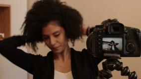 Vlogger sonriente que captura el vídeo con el dslr almacen de video