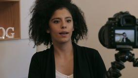 Vlogger sonriente que captura el vídeo con el dslr metrajes