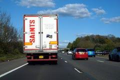 Vloot, het UK - 18 April 2017: De vrachtwagen van de HEILIGENlevering en diverse auto stock foto