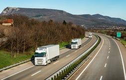 Vloot of konvooi van vrachtwagens op weg stock foto's