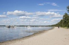 Vloot van botenkustvaart in het meer naast een zandig strand royalty-vrije stock foto