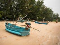 Vloot van pijlinktvis vissersboten op het strand in de bewolkte ochtenddag, met overzeese achtergrond Stock Afbeeldingen