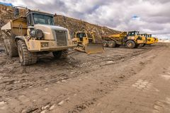 Vloot van vrachtwagens en een graafwerktuig op een bouwwerf stock afbeelding