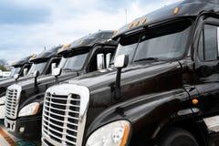 Vloot van zwarte 18 speculant semi vrachtwagens stock afbeelding