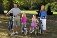 Vélos heureux d'équitation de famille en stationnement Images libres de droits