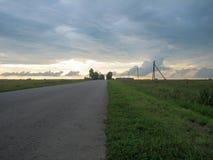 Vlotte rechte asfaltweg in het platteland onder de hemel met wolken bij zonsondergang royalty-vrije stock afbeeldingen