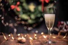 Vlotte schaduwrijke Kerstmis en de nieuwe achtergrond van de jaardecoratie met rond bokeh, gouden lint en champagne en cork stock foto