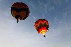 Vlotter van twee de kleurrijke hete luchtballons weg in de blauwe hemel Royalty-vrije Stock Fotografie