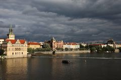 Vltava River Embankment in beams setting the sun against the background of the coming bad weather. royalty free stock photo