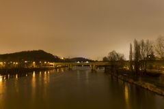 A Vltava river in Prague with a train bridge crossing it at night Royalty Free Stock Photos