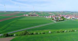 Vlucht dichtbij een klein modern Europees dorp, een kleine stad dichtbij windgenerators, windgenerators tegen de achtergrond van stock videobeelden
