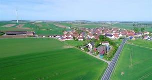 Vlucht dichtbij een klein modern Europees dorp, een kleine stad dichtbij windgenerators, windgenerators tegen de achtergrond van stock video