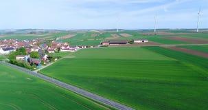 Vlucht dichtbij een klein modern Europees dorp, een kleine stad dichtbij windgenerators, windgenerators tegen de achtergrond van stock footage