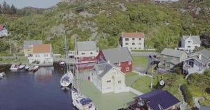 Vlucht over aardige die huizen op fjordbank worden neergestreken op zonnige dag stock footage