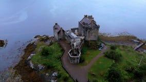 Vlucht over beroemde Eilean Donan Castle in de Hooglanden van Schotland - luchthommellengte stock footage