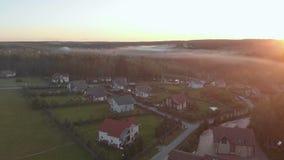 Vlucht over dorp met bos in zonsopgang zacht licht Beeld in oranje gloed wordt verwerkt die Majestueus Landschap Mist over stock videobeelden