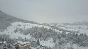 Vlucht over een dorp in Karpatische bergen De mening van het vogel` s oog van snow-covered huizen in bergen Landelijk landschap b stock video