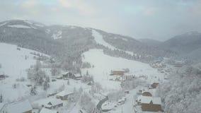 Vlucht over een dorp in Karpatische bergen De mening van het vogel` s oog van snow-covered huizen in bergen Landelijk landschap b stock videobeelden