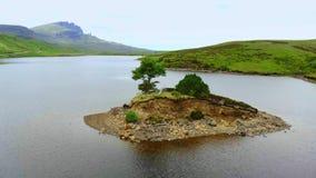 Vlucht over een uiterst klein eiland op een meer bij het Eiland van Skye in Schotland stock video