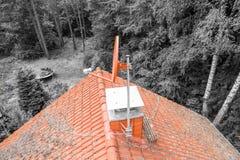 Vlucht over het rode dak van één enkel familiehuis met een schoorsteen en een satellietantenne voor inspectie, controle en voorbe stock foto's