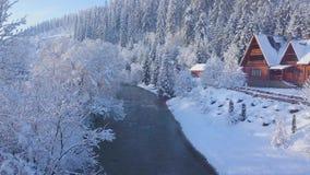 Vlucht over meisje het lopen langs een brug over een bergrivier dichtbij een berg met naaldbos in de winter wordt behandeld die stock footage