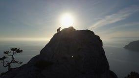 Vlucht over van jonge vrouw status op de bovenkant van een berg die het overzees onder ogen zien Dame op de top in mooi landschap stock videobeelden