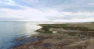 Vlucht van de camera eerst over de kust met de overgang aan water stock footage