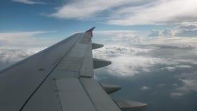Vlucht van het vliegtuig op een vliegniveau, tegen de achtergrond van blauwe hemel en weefsel volumetrische wolken De mening van stock video