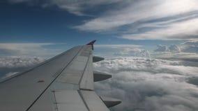 Vlucht van het vliegtuig op een vliegniveau, tegen de achtergrond van blauwe hemel en weefsel volumetrische wolken De mening van stock videobeelden
