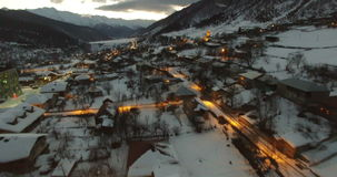 Vlucht van hommel in de winter in een bergdorp bij nacht in 4K stock video