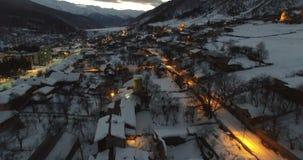 Vlucht van hommel in de winter over een bergdorp bij nacht in 4K stock videobeelden