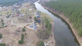 Vlucht voorbij rivier over kleine stad stock footage