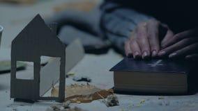 Vluchteling die met Bijbel voor huis bidden, die van schuilplaats, document huis als symbool dromen stock footage