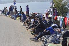 Vluchtelingen sittng op de straat Lesvos Griekenland royalty-vrije stock foto