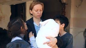 Vluchtelingskinderen en hun moeder met een kind in hun wapens amid vernietigde huizen Oorlog, aardbeving, brand, het bombarderen stock videobeelden