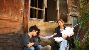 Vluchtelingskinderen en hun moeder met een kind in hun wapens amid vernietigde huizen Oorlog, aardbeving, brand, het bombarderen stock video