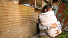 Vluchtelingskinderen met een kind in hun wapens in het midden van vernietigde huizen Oorlogen, aardbevingen, branden, bombardemen stock video