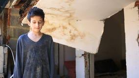 Vluchtelingskinderen tegen de achtergrond van gebombardeerde huizen Oorlog, aardbeving, brand stock video