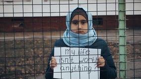 Vluchtelingsmeisje met een inschrijving op een wit blad stock videobeelden
