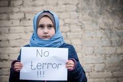 Vluchtelingsmeisje met een inschrijving op een wit blad royalty-vrije stock foto's