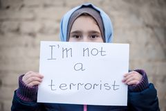 Vluchtelingsmeisje met een inschrijving op een wit blad royalty-vrije stock afbeelding
