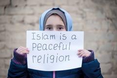 Vluchtelingsmeisje met een inschrijving op een wit blad stock foto