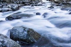 Vlug bewegend rivierwater over en rond het grote landschap van de rotsenwinter Stock Foto's