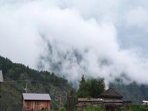 Vlugge waterstroom in bergrivier met klein dorp op achtergrond stock videobeelden