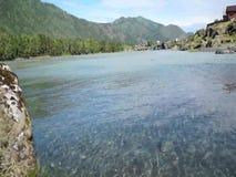 Vlugge waterstroom in bergrivier met klein dorp op achtergrond stock footage