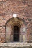 Välvt fönster i romansk-stil kyrka Arkivfoto